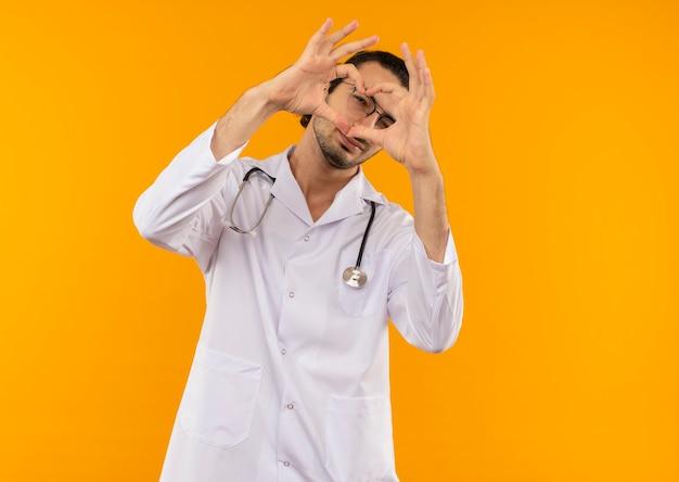 Młody lekarz z okularami medycznymi na sobie szlafrok medyczny ze stetoskopem pokazujący gest serca