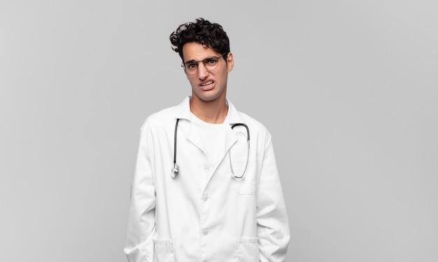 Młody lekarz zdziwiony i zdezorientowany, z głupim, oszołomionym wyrazem twarzy, patrząc na coś nieoczekiwanego