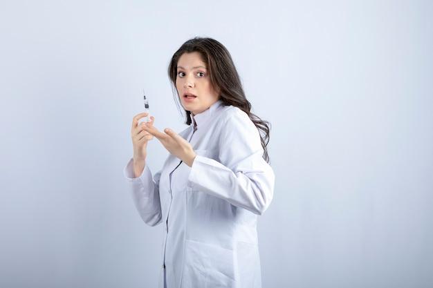 Młody lekarz ze strzykawki stojącej na białej ścianie.