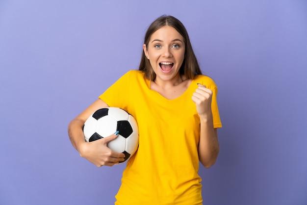 Młody litewski piłkarz kobieta na białym tle na fioletowej ścianie świętuje zwycięstwo w pozycji zwycięzcy