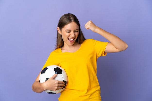 Młody litewski piłkarz kobieta na białym tle na fioletowej ścianie świętuje zwycięstwo