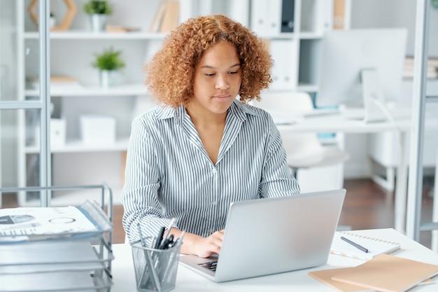 Młody los mieszanej rasy siedzi przy biurku przed wyświetlaczem laptopa