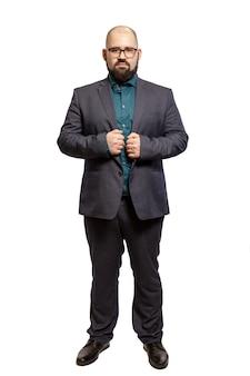 Młody łysy brodaty mężczyzna w okularach i pełnej długości garnitur. pojedynczo na białym tle