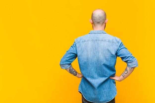Młody łysy i brodaty mężczyzna czujący się zdezorientowany lub pełny lub wątpliwości i pytania, zastanawiający się, z rękami na biodrach, widok z tyłu