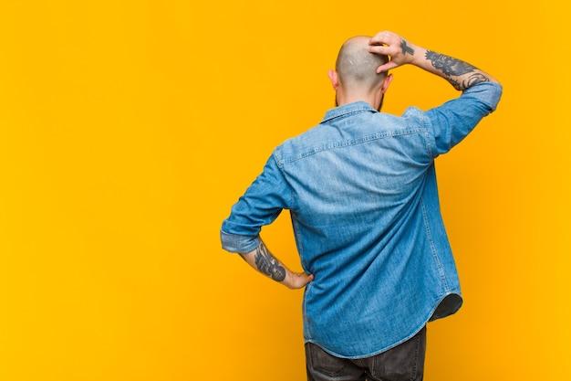 Młody łysy i brodaty mężczyzna czuje się nieświadomy i zdezorientowany, myśląc o rozwiązaniu, z ręką na biodrze i drugą na głowie, widok z tyłu
