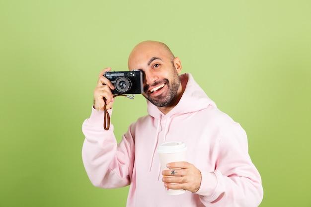 Młody łysy kaukaski mężczyzna w różowej bluzie z kapturem na białym tle, pozytywny aparat fotograficzny i filiżankę kawy