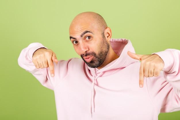 Młody łysy kaukaski mężczyzna w różowej bluzie z kapturem na białym tle, pozytywny zszokowany zdumiony podekscytowany wskazujący palcami w dół