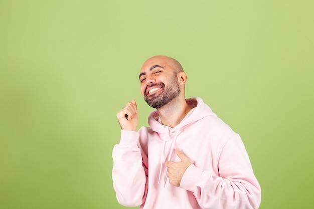 Młody łysy kaukaski mężczyzna w różowej bluzie z kapturem na białym tle, szczęśliwy i wesoły, uśmiechnięty, poruszający się swobodny i pewny siebie, słuchając muzyki