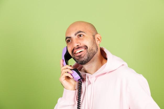 Młody łysy kaukaski mężczyzna w różowej bluzie z kapturem na białym tle, trzymaj telefon stacjonarny z radosną podekscytowaną zdumioną twarzą