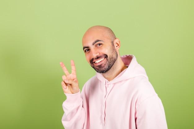 Młody łysy kaukaski mężczyzna w różowej bluzie z kapturem robi znak zwycięstwa