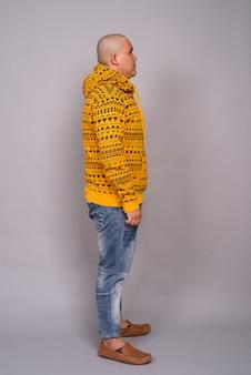 Młody łysy mężczyzna azji ubrany w bluzę z kapturem na szarej ścianie