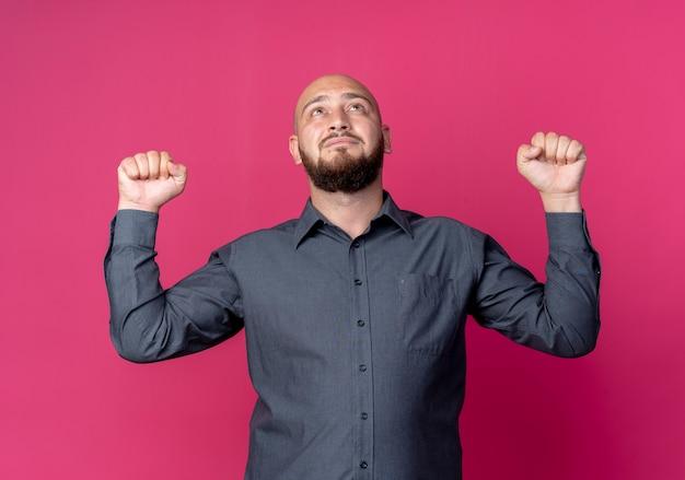 Młody łysy mężczyzna call center podnosząc pięści i patrząc w górę na białym tle na szkarłatnym tle