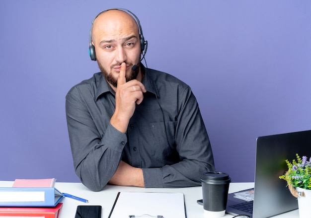 Młody łysy mężczyzna call center sobie zestaw słuchawkowy siedzi przy biurku z narzędzi pracy, wskazując ciszę na białym tle na fioletowym tle