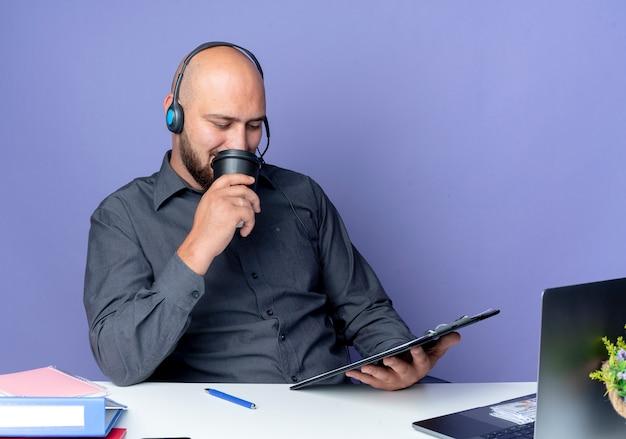 Młody łysy mężczyzna call center sobie zestaw słuchawkowy siedzi przy biurku z narzędziami pracy, trzymając i patrząc w schowku i pije kawę na białym tle na fioletowym tle