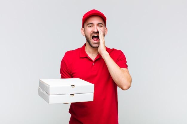 Młody łysy mężczyzna czuje się szczęśliwy, podekscytowany i pozytywny, krzyczy głośno z rękami przy ustach i woła