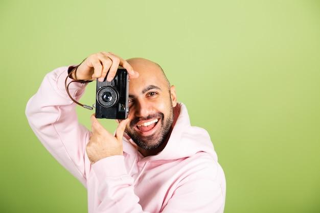 Młody łysy mężczyzna kaukaski w różową bluzę z kapturem na białym tle, pozytywne hipster trzymać aparat