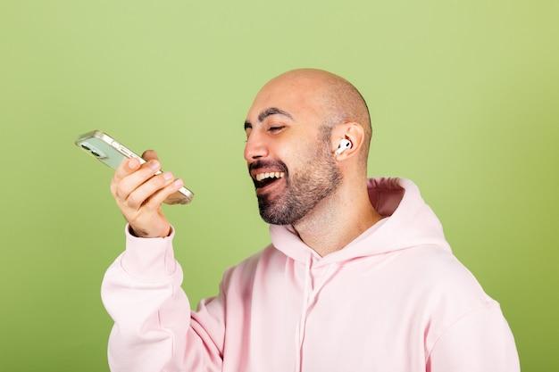 Młody łysy mężczyzna kaukaski w różowej bluzie z kapturem na białym tle, trzymaj telefon szczęśliwy pozytywny nagrywanie wiadomości audio