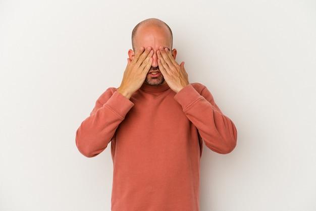 Młody łysy mężczyzna na białym tle boi się zasłaniając oczy rękami.