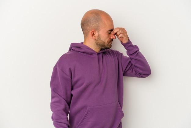 Młody łysy mężczyzna na białym tle o ból głowy, dotykając przodu twarzy.