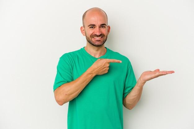 Młody łysy mężczyzna na białym tle podekscytowany, trzymając miejsce na dłoni.