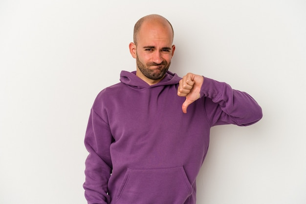 Młody łysy mężczyzna na białym tle pokazując kciuk w dół, koncepcja rozczarowanie.