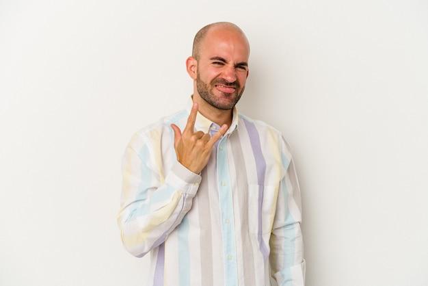 Młody łysy mężczyzna na białym tle pokazujący rockowy gest palcami