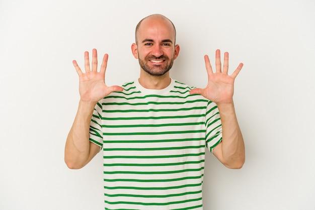 Młody łysy mężczyzna na białym tle pokazuje numer dziesięć z rękami.
