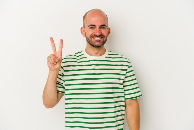 Młody łysy mężczyzna na białym tle radosny i beztroski pokazując symbol pokoju palcami.