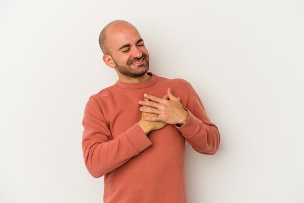 Młody łysy mężczyzna na białym tle śmiejąc się trzymając ręce na sercu, pojęcie szczęścia.