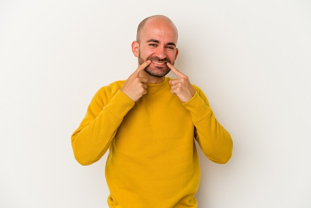 Młody łysy mężczyzna na białym tle uśmiecha się, wskazując palcami na usta.