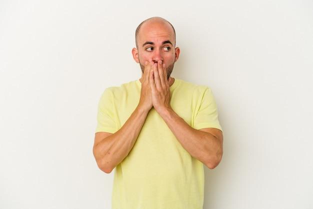 Młody łysy mężczyzna na białym tle zamyślony patrząc na miejsce na kopię obejmujące usta ręką.
