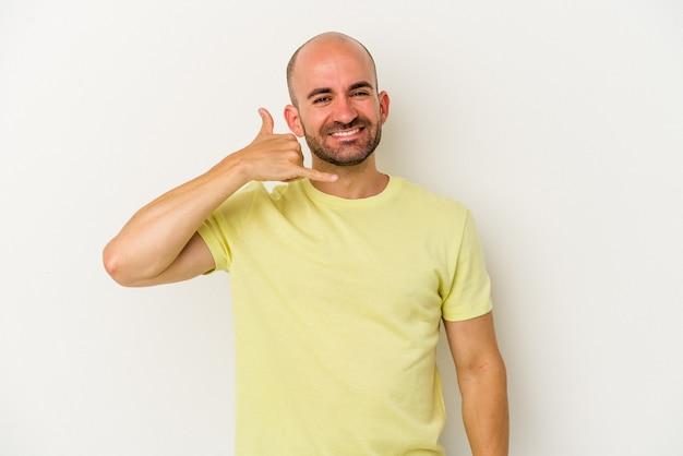 Młody łysy mężczyzna odizolowywający na białym tle pokazujący gest rozmowy przez telefon komórkowy palcami.