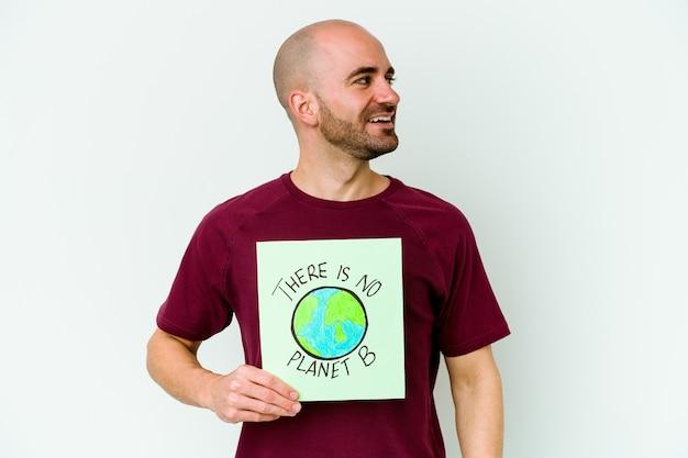 Młody łysy mężczyzna rasy kaukaskiej trzymający tabliczkę z planetą b na fioletowym tle wygląda z boku uśmiechnięty, wesoły i przyjemny.