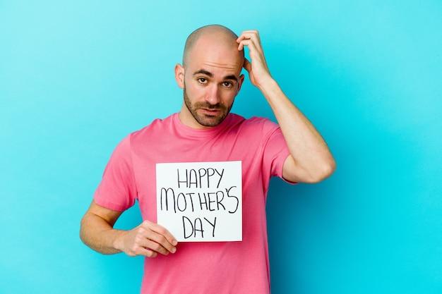 Młody łysy mężczyzna trzyma tabliczkę szczęśliwego dnia matki na białym tle na niebieskiej ścianie, będąc w szoku, przypomniała sobie ważne spotkanie