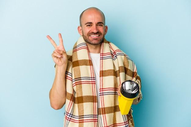 Młody łysy mężczyzna trzyma vintage latarnię na białym tle na niebieskim tle radosny i beztroski pokazując symbol pokoju palcami.