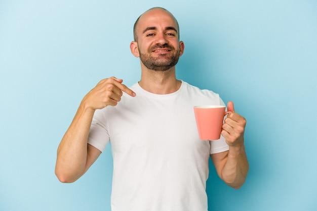 Młody łysy mężczyzna trzymający kubek na białym tle na niebieskim tle osoba wskazująca ręką miejsce na koszulkę, dumna i pewna siebie