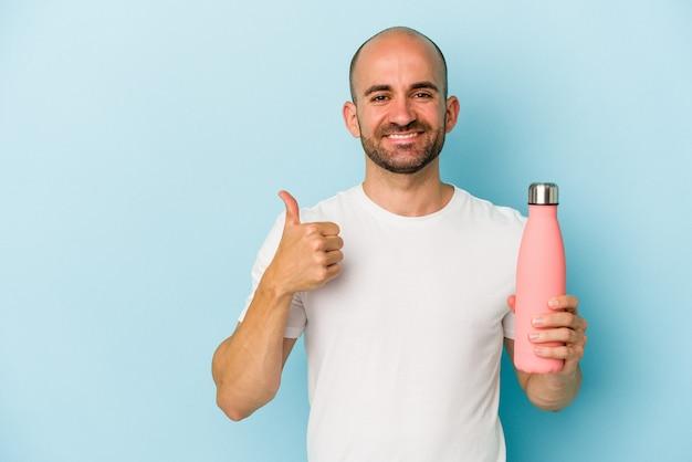Młody łysy mężczyzna trzymający stołówkę na białym tle, uśmiechający się i unoszący kciuk w górę