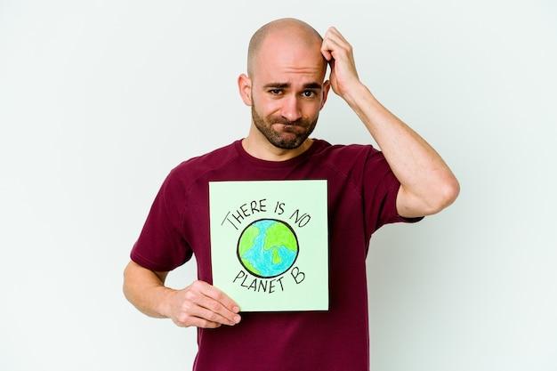 Młody łysy mężczyzna trzymający tabliczkę na izolacji na ścianie nie ma planety b, wstrząśnięty, przypomniała sobie ważne spotkanie
