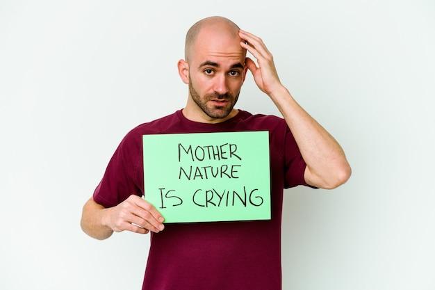 Młody łysy mężczyzna z płaczącą matką naturą na białej ścianie, wstrząśnięty, przypomniała sobie ważne spotkanie