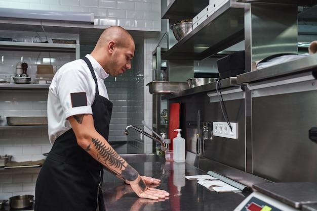 Młody łysy szef kuchni z tatuażami patrzący na listy zamówień na stalowym stole w kuchni restauracji restaurant