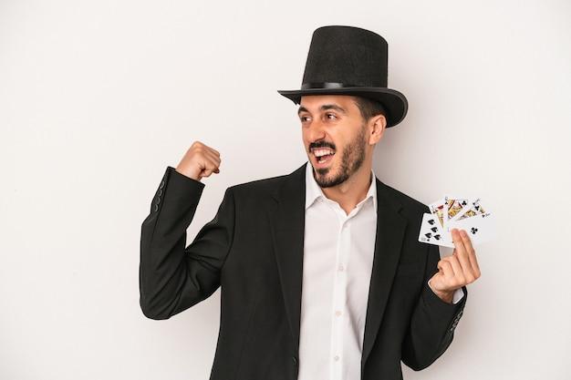 Młody mag mężczyzna trzyma magiczną kartę na białym tle podnosząc pięść po zwycięstwie, koncepcja zwycięzca.