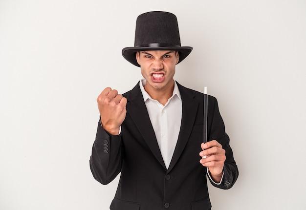 Młody magik kaukaski mężczyzna trzyma różdżkę na białym tle na białym tle pokazując pięść do kamery, agresywny wyraz twarzy.