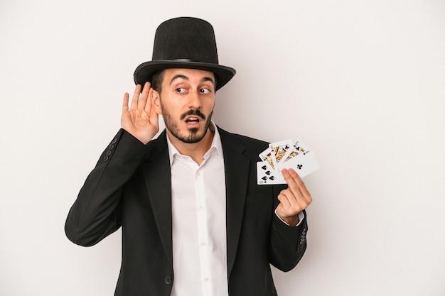 Młody magik mężczyzna trzyma magiczną kartę na białym tle próbuje słuchać plotek.