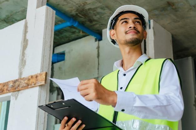 Młody majster budowniczy, inżynier lub inspektor sprawdzający i kontrolujący ze schowkiem na budowie budynku wnętrza przed ukończeniem nowej koncepcji projektu, kontroli, wykonawcy i inżynierii