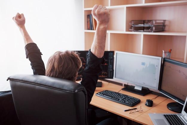 Młody makler giełdowy wyciąga ręce w miejscu pracy, po raz pierwszy odniósł wielki sukces na giełdzie