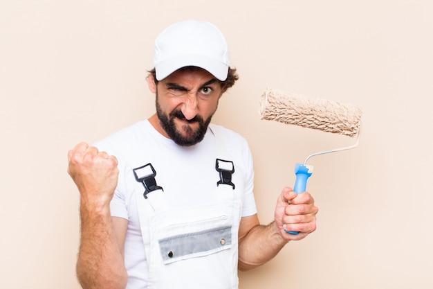 Młody malarz brodaty mężczyzna trzyma wałek do malowania z gniewnym wyrazem