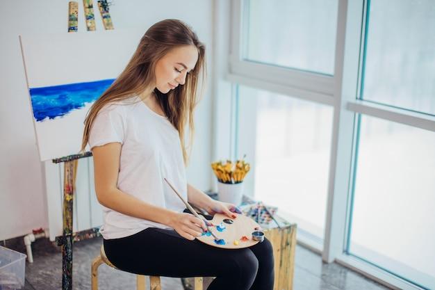 Młody malarz kobiety obraz na sztaludze w warsztacie