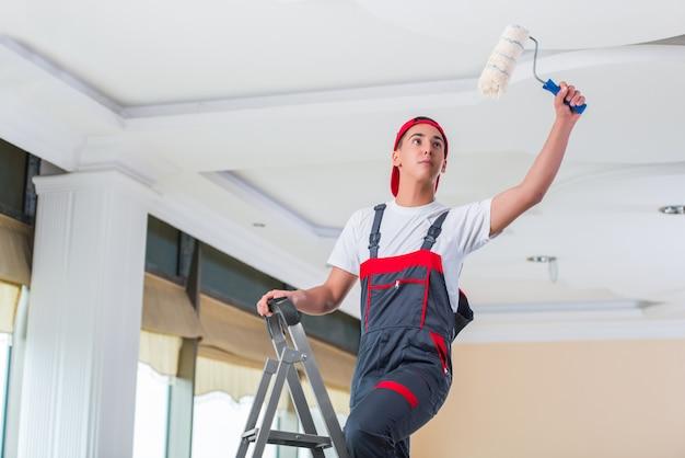 Młody malarz maluje sufit w budowy pojęciu