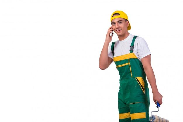 Młody malarz opowiada na telefonie komórkowym odizolowywającym na bielu