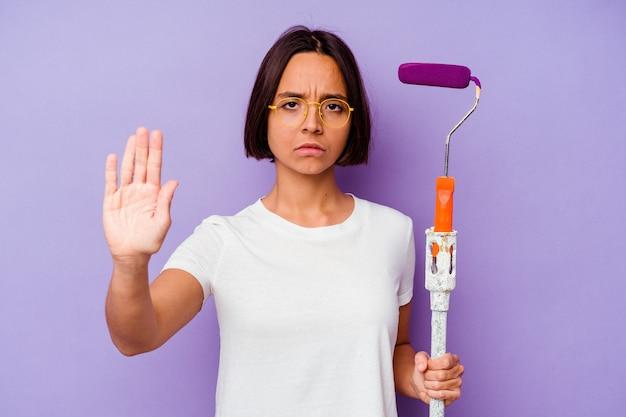 Młody malarz rasy mieszanej kobieta trzyma kij z farbą na białym tle na fioletowym tle stojąc z wyciągniętą ręką pokazując znak stopu, uniemożliwiając tobie.